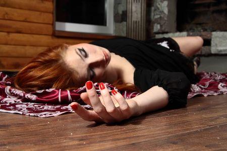 Dead young woman on wooden floor. Studio shot.