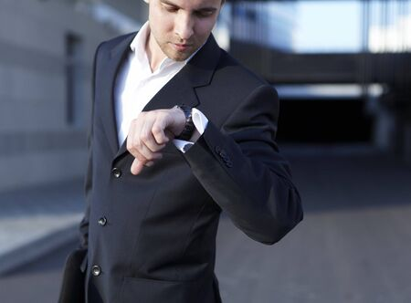 A handsome business man looking at watch