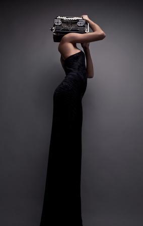 Elegant woman pose with ancient typewriter  Conceptual fashion photo