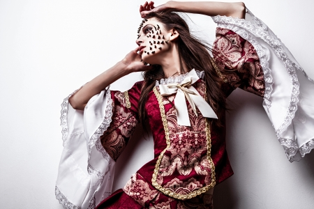 Fine art photo of a young lady in medieval dress with thorns of roses on her face