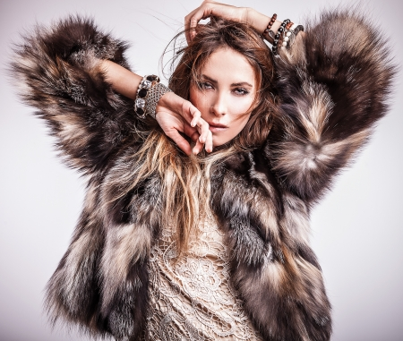 Portrait of attractive stylish woman in fur against grey background