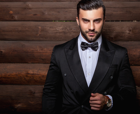 Portrait of young beautiful fashionable man against wooden wall In black suit  bow tie.