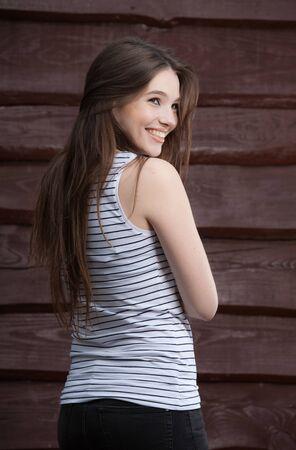 Photo pour Portrait of beautiful young girl on wooden background. - image libre de droit