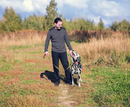 young man walking a dog Dalmatian outdoors in the park green