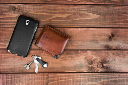 Leather purse, phone pouch and keys on a wooden table background. Required items for the man at the exit of the house that can not be forgotten.