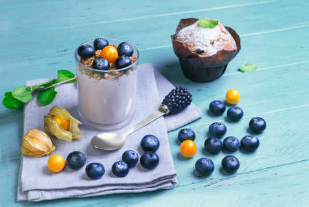 On blue wooden background Breakfast muffin berry, cape gooseberry, blueberry yogurt in a glass, sprig of mint, spoon with blackberry