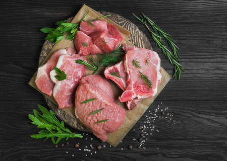 Assortment different types assorted of cuts and portions of raw fresh red meat pork displayed with fresh herbs, spice, brown wooden background