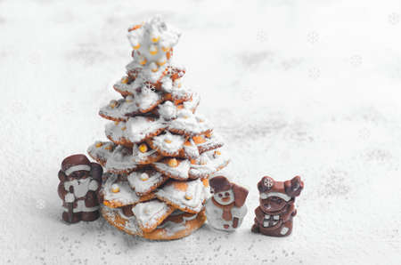 Photo pour New Year Christmas card. Gingerbread Christmas tree Cookies decorated with icing sugar and sweets. Christmas Chocolate Marzipan figure next to the gingerbread Christmas tree. Sweet snow. Blank space - image libre de droit