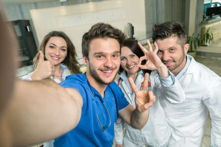 Photo for Smiling Team Of Doctors And Nurses At Hospital Taking Selfie. - Royalty Free Image