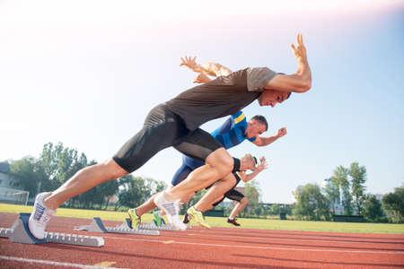 Photo pour Runners preparing for race at starting blocks. - image libre de droit