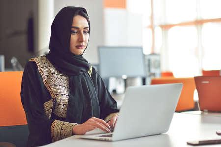 Photo pour Muslim asian woman working in office with laptop - image libre de droit