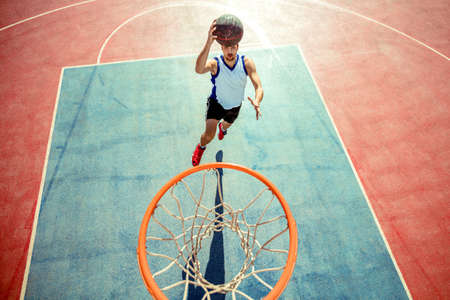 Photo pour High angle view of basketball player dunking basketball in hoop - image libre de droit