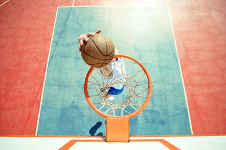 Foto für Young man jumping and making a fantastic slam dunk playing streetball, basketball. Urban authentic. - Lizenzfreies Bild