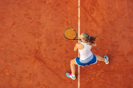 Foto für Aerial shot of a female tennis player on a court during match. Young woman playing tennis.High angle view. - Lizenzfreies Bild