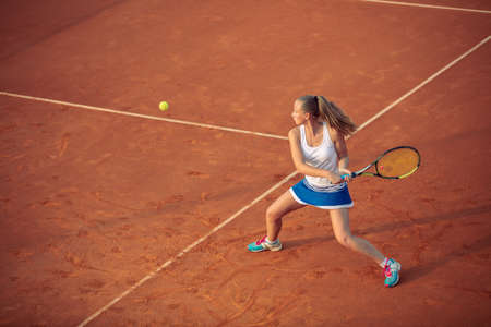 Photo for Woman playing tennis on clay court, with sporty outfit and healthy lifestyle - Royalty Free Image