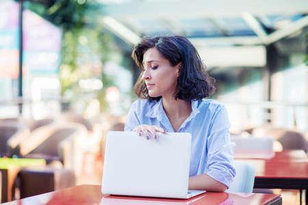 Foto de Contemplated young woman in cafe with laptop - Imagen libre de derechos