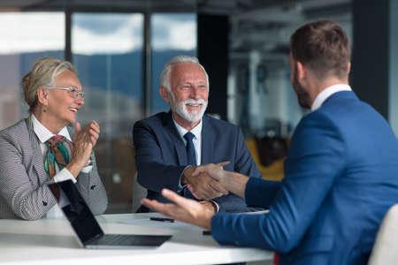 Foto de Positive aged couple consulting with insurance agent - Imagen libre de derechos