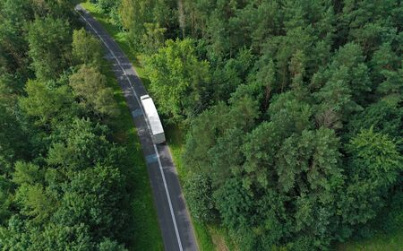 Photo pour Aerial drone perspective view on white truck with cargo trailer riding through the forest on curved asphalt road. - image libre de droit