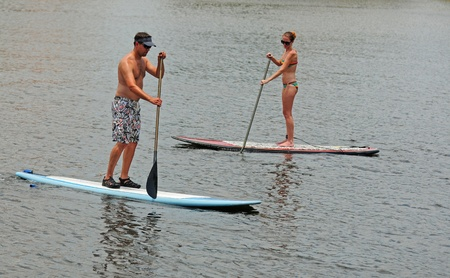 young man and woman couple paddleboarding in ocean