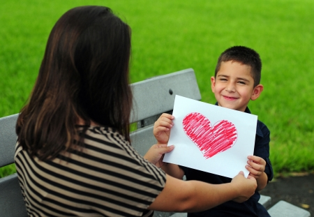young boy giving his mother a heart drawing for a present