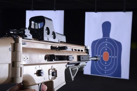 firearm or machine gun pointed at bullseye target on gun range