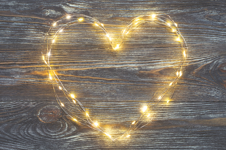 Photo pour Garland lights in the shape of heart on a rustic wooden table. Concept of Love and Valentines day - image libre de droit