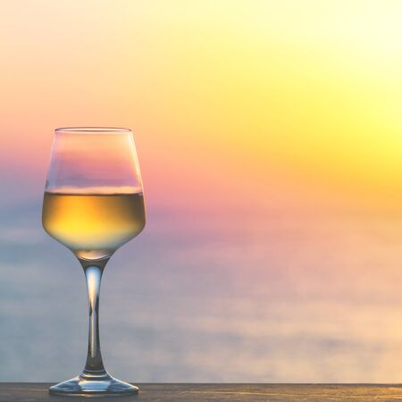 Photo for Glass of white wine against sunset. Beautiful summer evening sea view. - Royalty Free Image