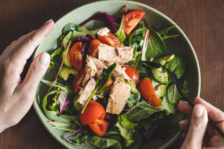 Photo pour Close up of woman eating salad with tuna. Top view. - image libre de droit