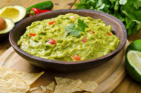 Guacamole with avocado, lime, tomato, and cilantro with tortilla chips.