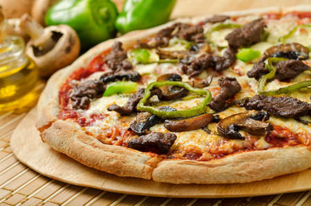 Photo pour A delicious steak and mushroom pizza with green peppers and olive oil  - image libre de droit
