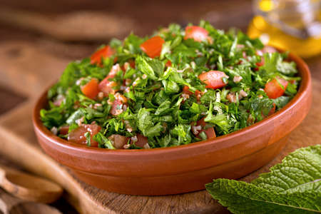 A bowl of delicious fresh tabouli with parsley, mint, tomato, onion, olive oil, lemon juice, and bulgar wheat.