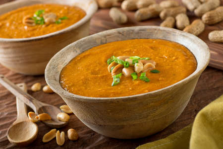 Photo pour A delicious bowl of homemade african peanut soup with green onion garnish. - image libre de droit