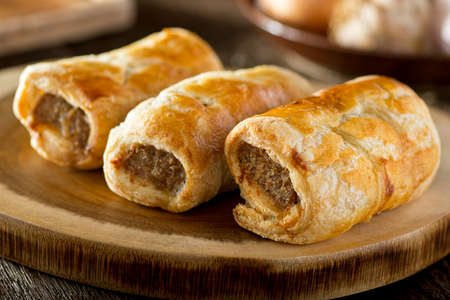 Delicious homemade sausage rolls on a wooden serving platter.