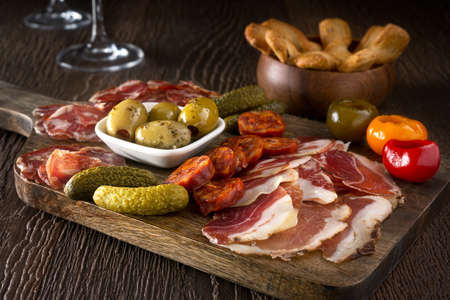 Photo pour A delicious charcuterie assortment of meat, olives, gherkins, and pickled peppers with breadsticks on a wooden background. - image libre de droit