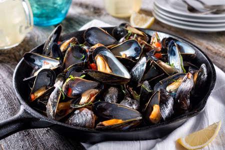 Foto de Delicious fresh steamed mussels on a rustic wood table top. - Imagen libre de derechos