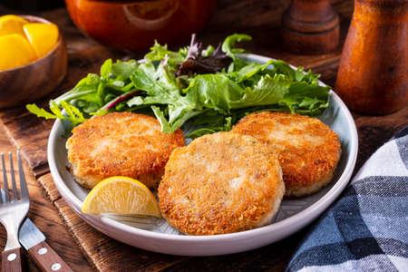 Photo pour A plate of delicious fish cakes with spring mix salad and lemon garnish. - image libre de droit