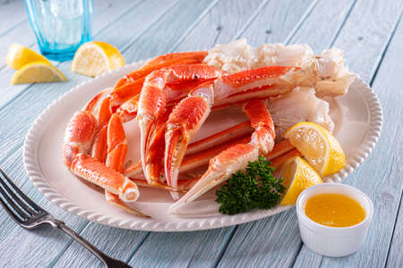 Foto für A plate of delicious snow crab leg clusters with lemon, parsley and melted butter. - Lizenzfreies Bild