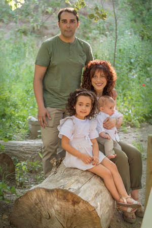 Foto de Family consisting of father mother baby and girl sitting on a log of wood in a grove. - Imagen libre de derechos