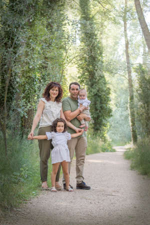 Foto de Family consisting of father mother baby and a girl posing in a grove surrounded by greenery. - Imagen libre de derechos