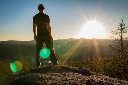 Photo for Young man stand on rock with forest and pond, looking to valley - Royalty Free Image