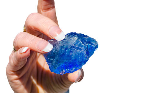 Quartz stone, glass stone pieces in blue held by a hand against white background