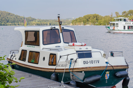 ESSEN, GERMANY - JUNE 21 2014  Free license charter boat houseboat the Green fleet moored on the Baldeneysee in Essen  The Green Fleet rented various unlicensed charter boats  In the background, the passenger vessel Steele