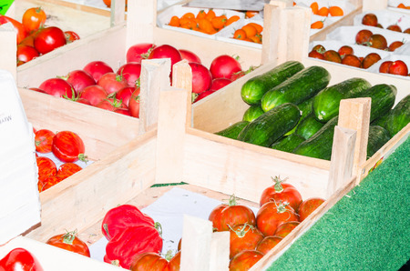 Stand with tomatoes, peppers and fresh green cucumbers on a market.