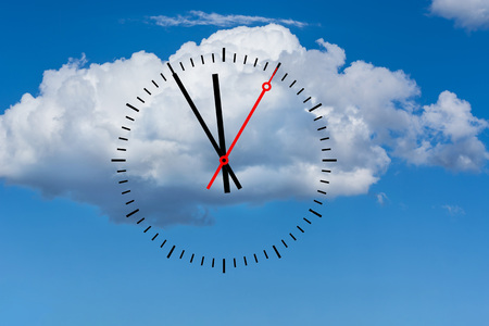 Clock, digits with a minute hand and a red second hand indicates the time 5 before 12. Copy space in front of sky and cloud background.
