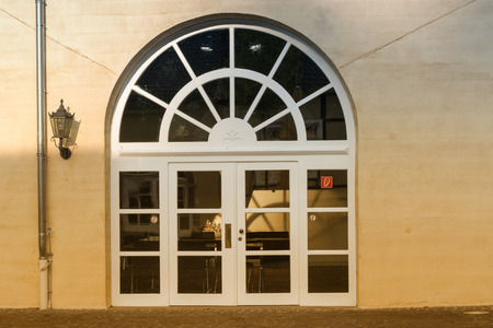 New large round arch door with rungs in a yellow plastered house wall.