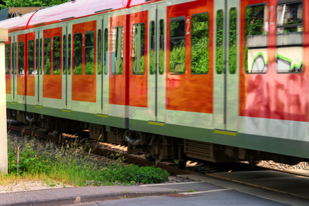 S-Bahn train passes a restricted railway crossing.