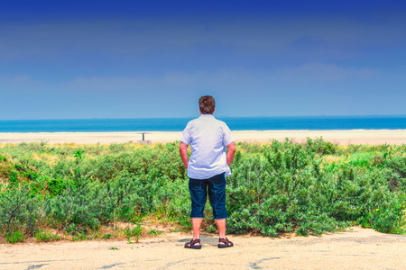 Man stands on the beach and looks out to sea