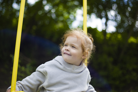 Photo for beautiful cute little redhead girl riding on a swing on the playground - Royalty Free Image