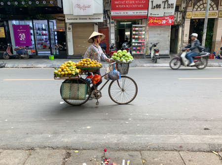 Photo for Hanoi, Vietnam - November 15,2019 : Asian woman walking bike, fruit vendor - Royalty Free Image