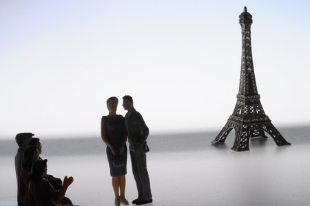 Scene of french people lovers miniature figures in front of Paris Eiffel tower